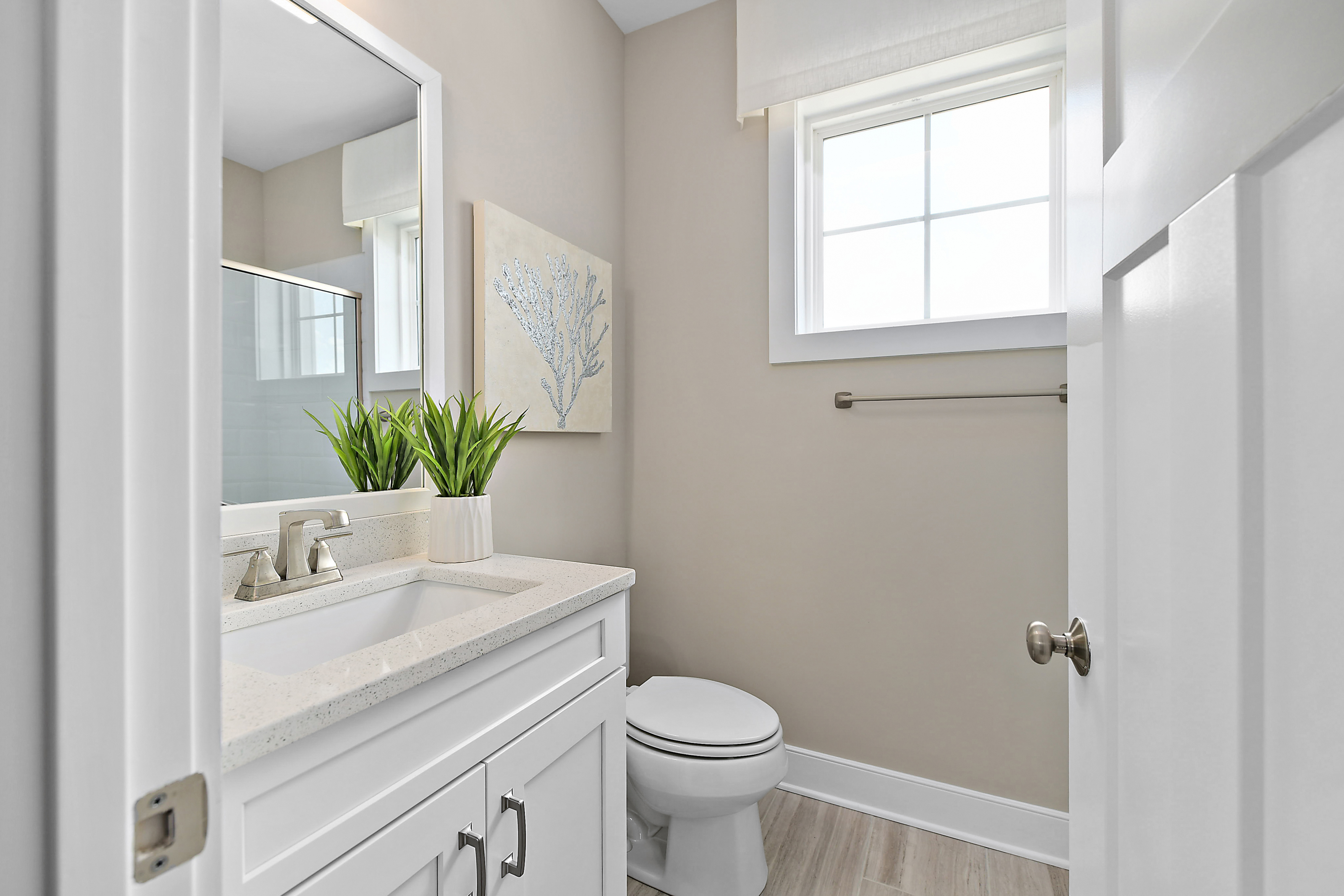 Main Level Bathroom with White Vanity, Quartz Counter and Wood Floors