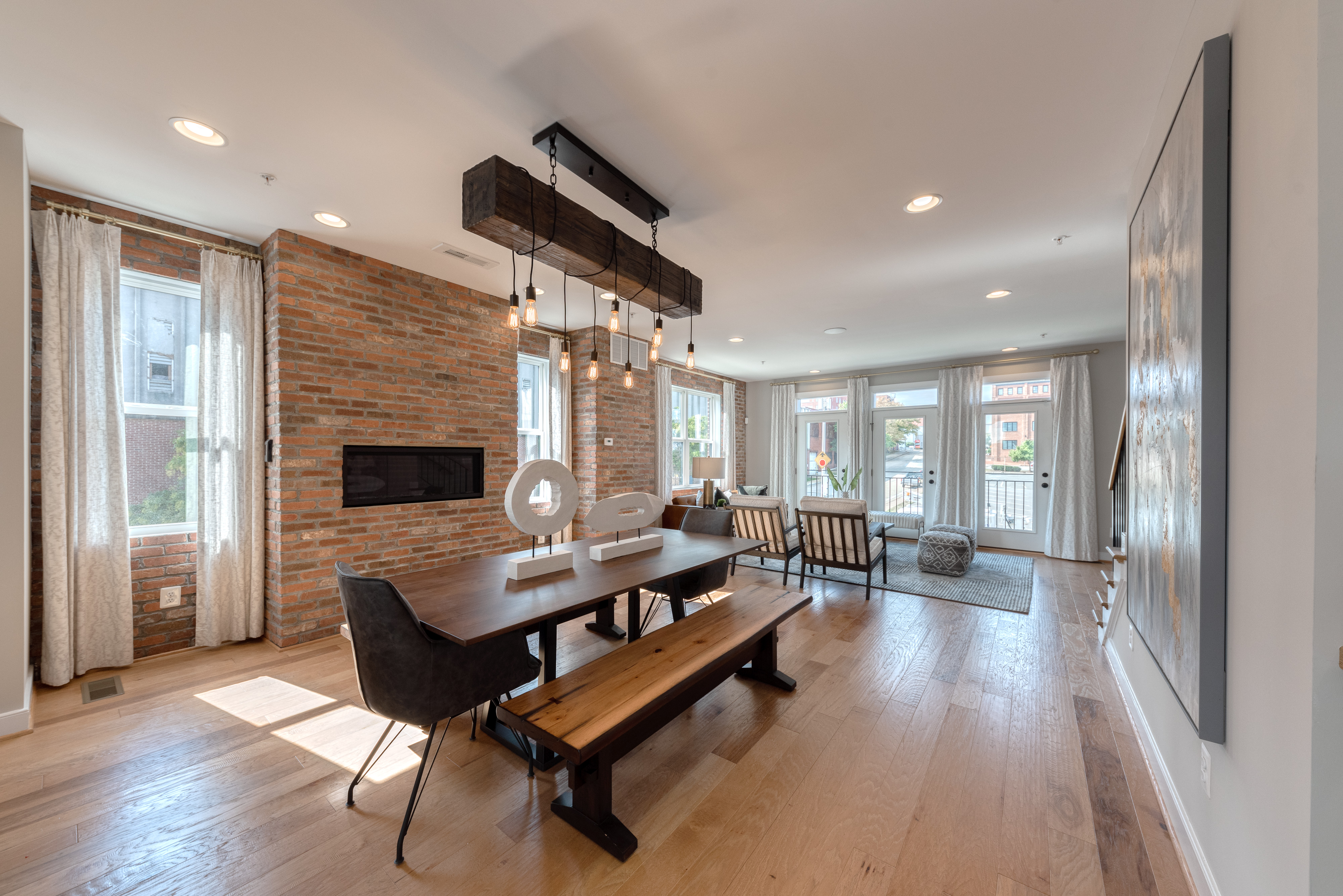 Dining Space with Table and Large Chandelier and Fireplace in Brick Wall