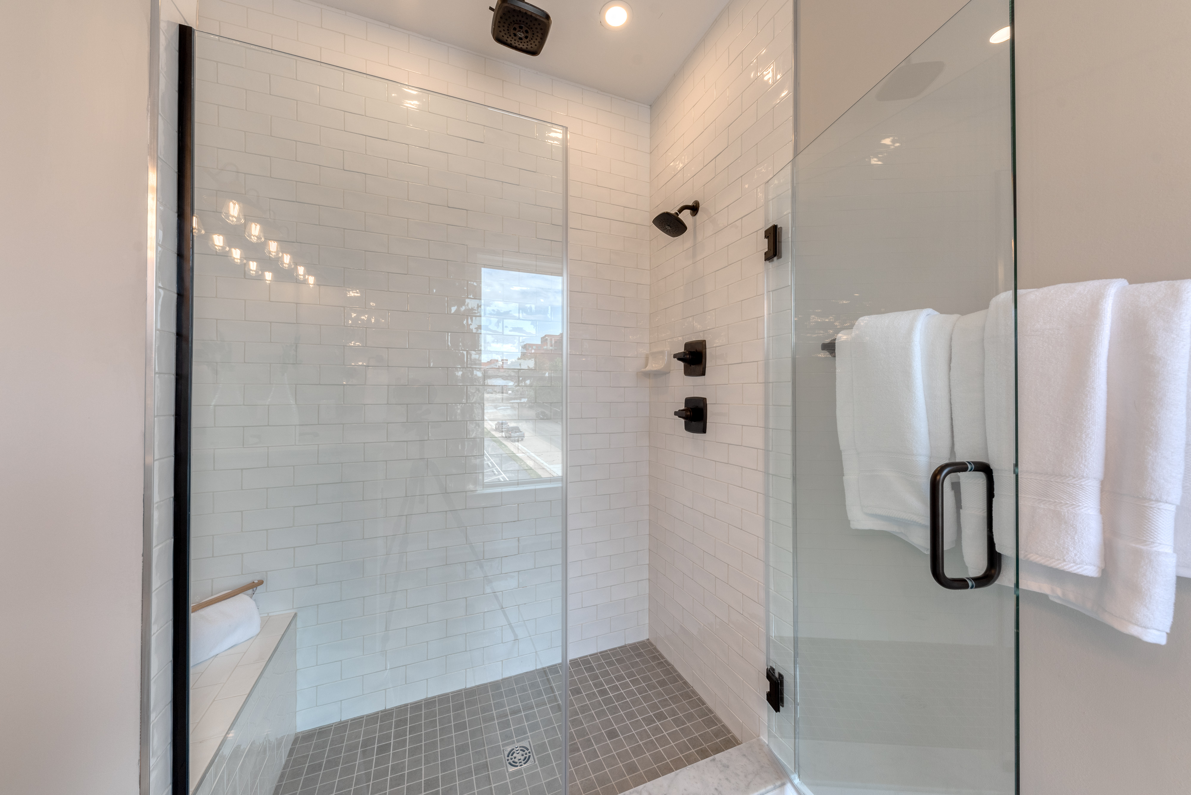 Owners Shower with Frameless Shower Door, White Tile, and Black Hardware