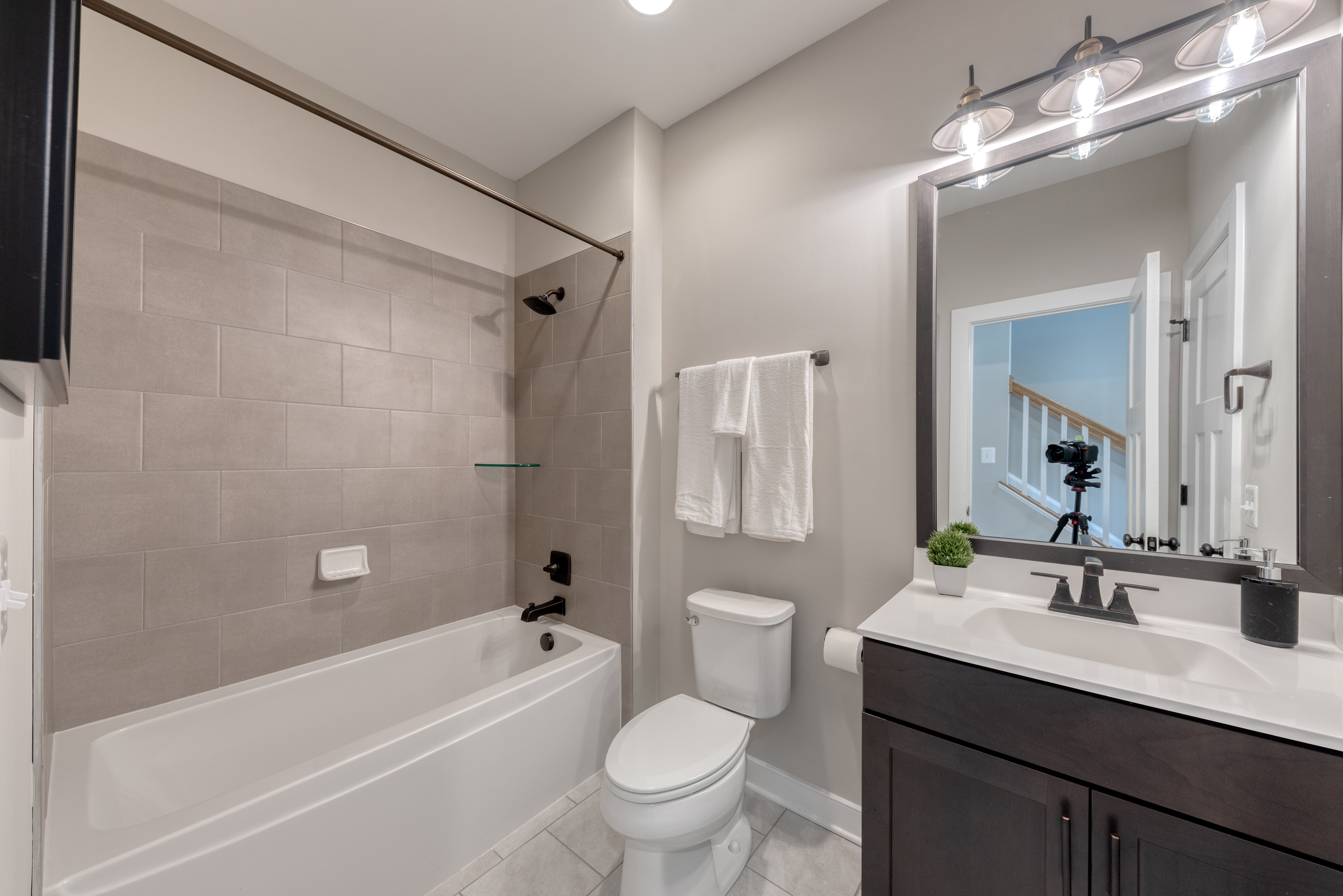Ground Level Bathroom with Tub, Dark Cabinets and Gray Tile
