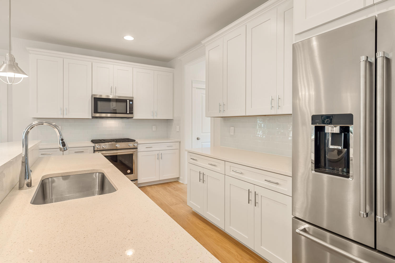 Kitchen with White Cabinets, Quartz Counters, and Stainless Steel Appliances