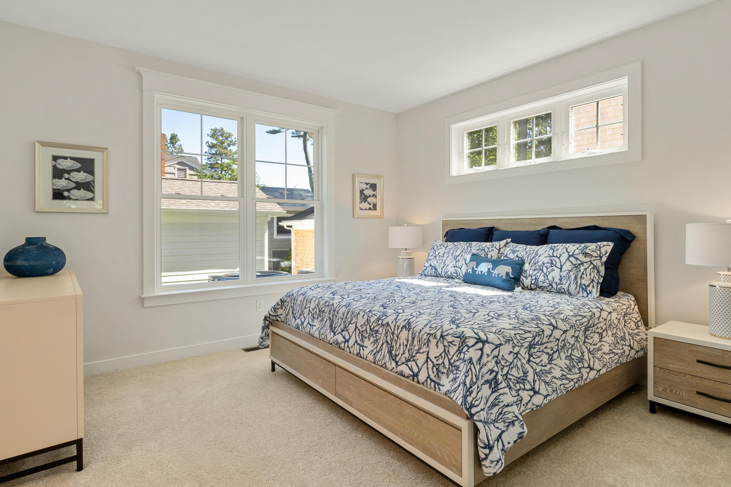 Staged Bedroom with Large Bed, Dresser and Large Exterior Windows