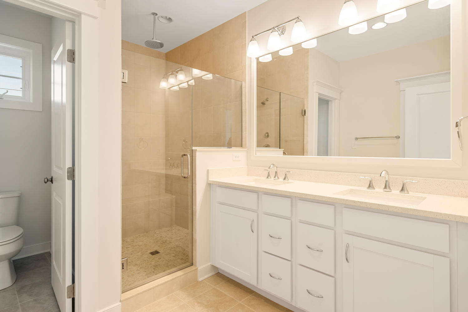 Owners Bath with White Cabinets and Bright Lighting