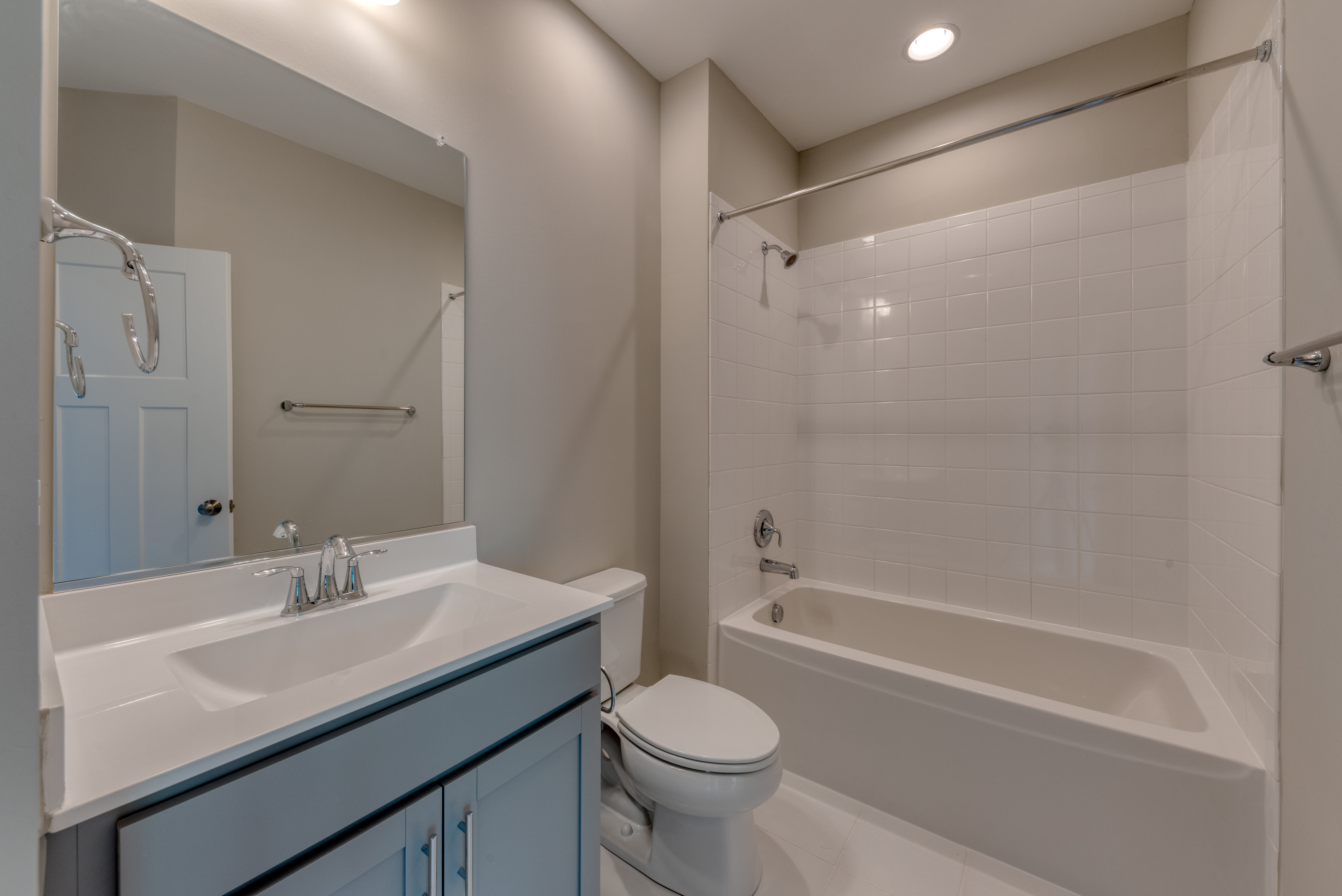 Hall Bathroom with Tub, Gray Cabinets and Tile